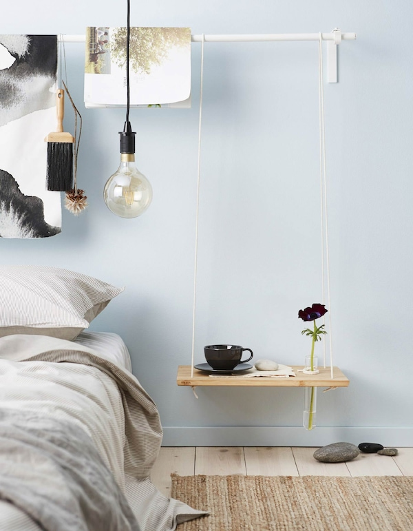 A DIY hanging bedside table made from a chopping board and rope has a hole drilled in it to hold a thin glass tube vase.