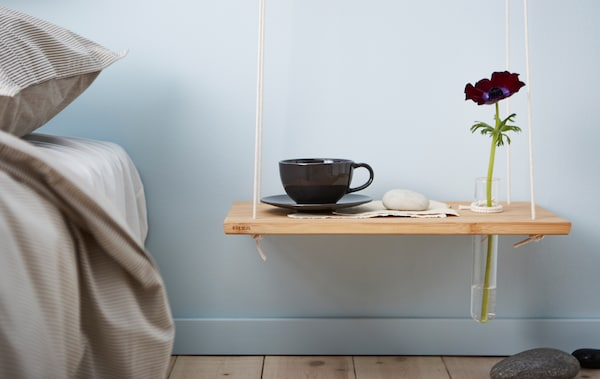 A DIY hanging bedside table made from a chopping board and rope hangs against a light blue wall in a bedroom.