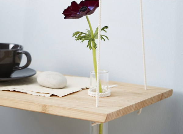A DIY hanging bedside table made from a chopping board with a cup and a flower in a glass vase.