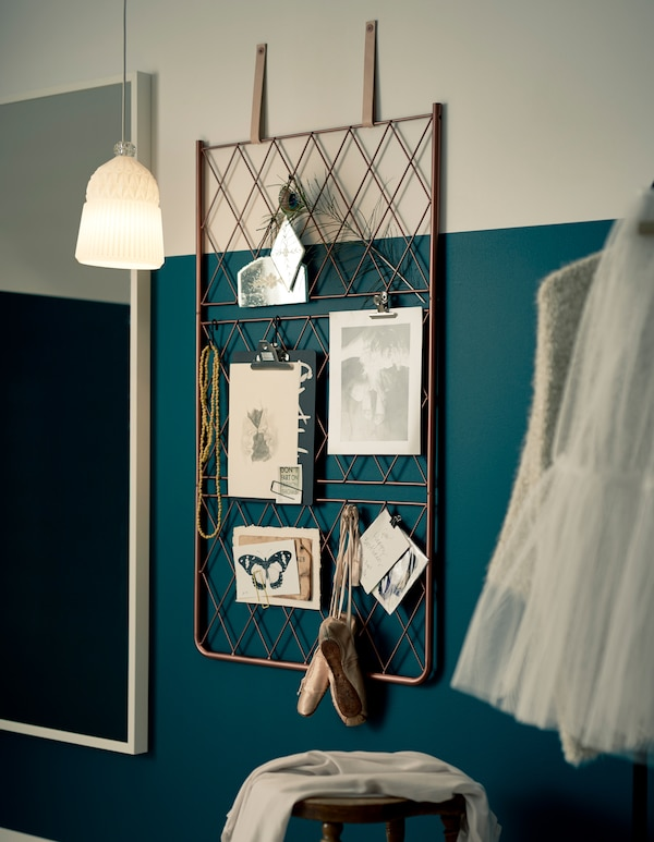 A DIY metal wire inspiration board hanging by leather straps on a wall.