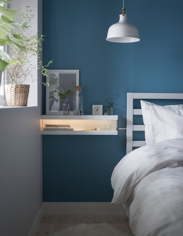 A DIY nightstand made from two MOSSLANDA picture ledges mounted on a blue wall in a bedroom.
