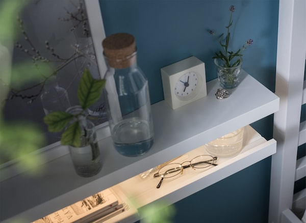 A DIY nightstand made from two MOSSLANDA picture ledges stacked on each other with an LED strip inside.