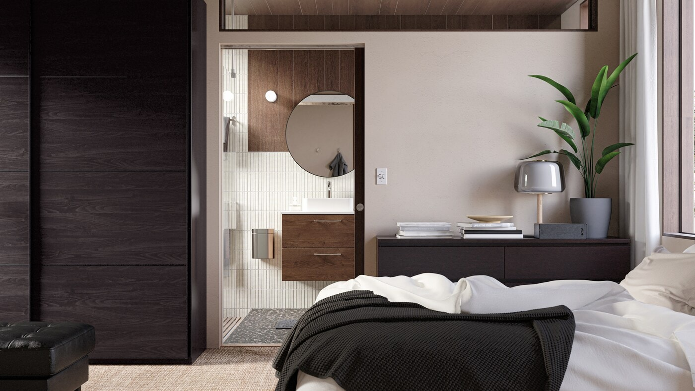 A door in the bedroom offers a peek into a stylish bathroom with a wooden sink cabinet, a round mirror and beige tiles.