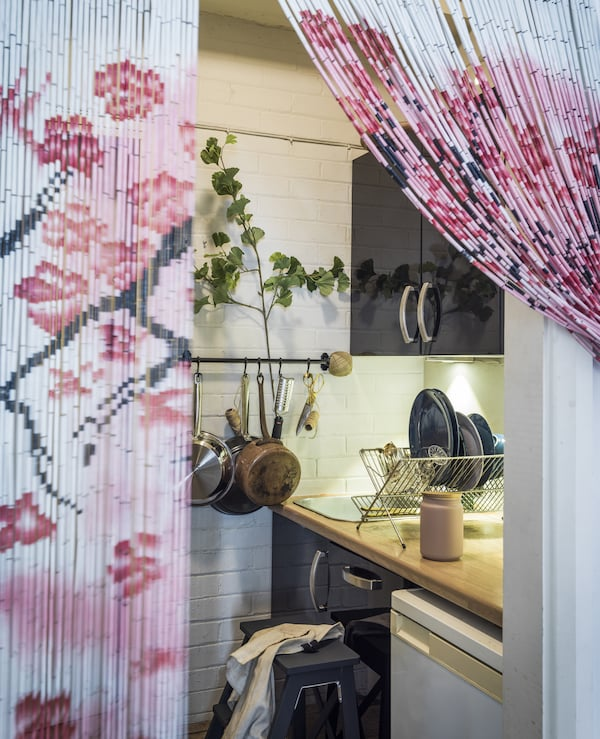 A door with a bead curtain leading to a small kitchen.