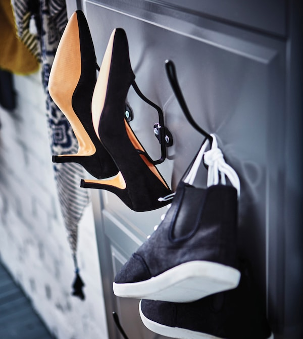 A doorfront is hung on the wall, with hooks on it to hold shoes.