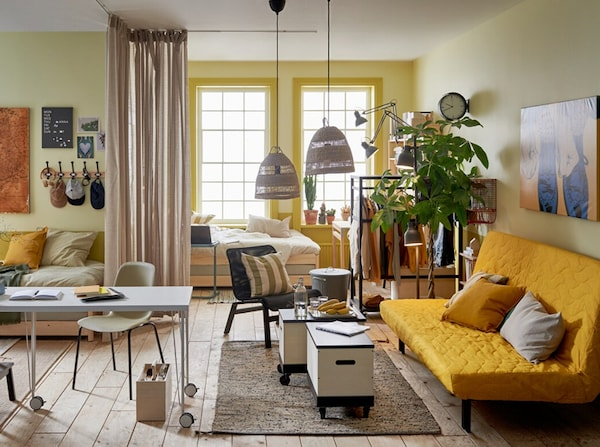 A dorm room with IKEA articles, yellow futon, desk, curtains and accessories