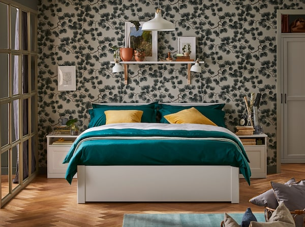 A double bed with green bedding and yellow cushions. A shelf is behind it on the wall and a pendant lamp hangs above.