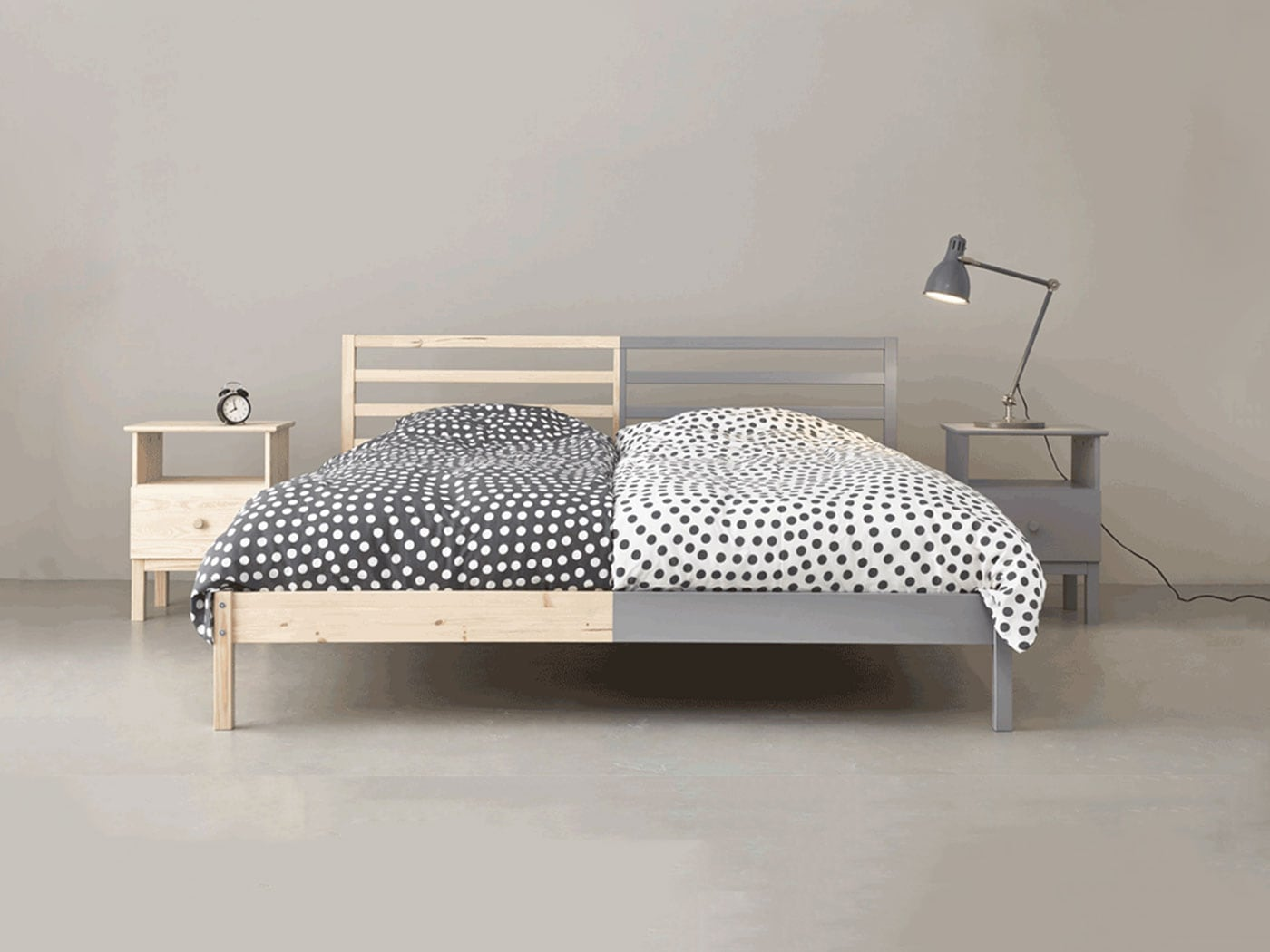 A double bed with half a side painted in grey, placed in a grey room.