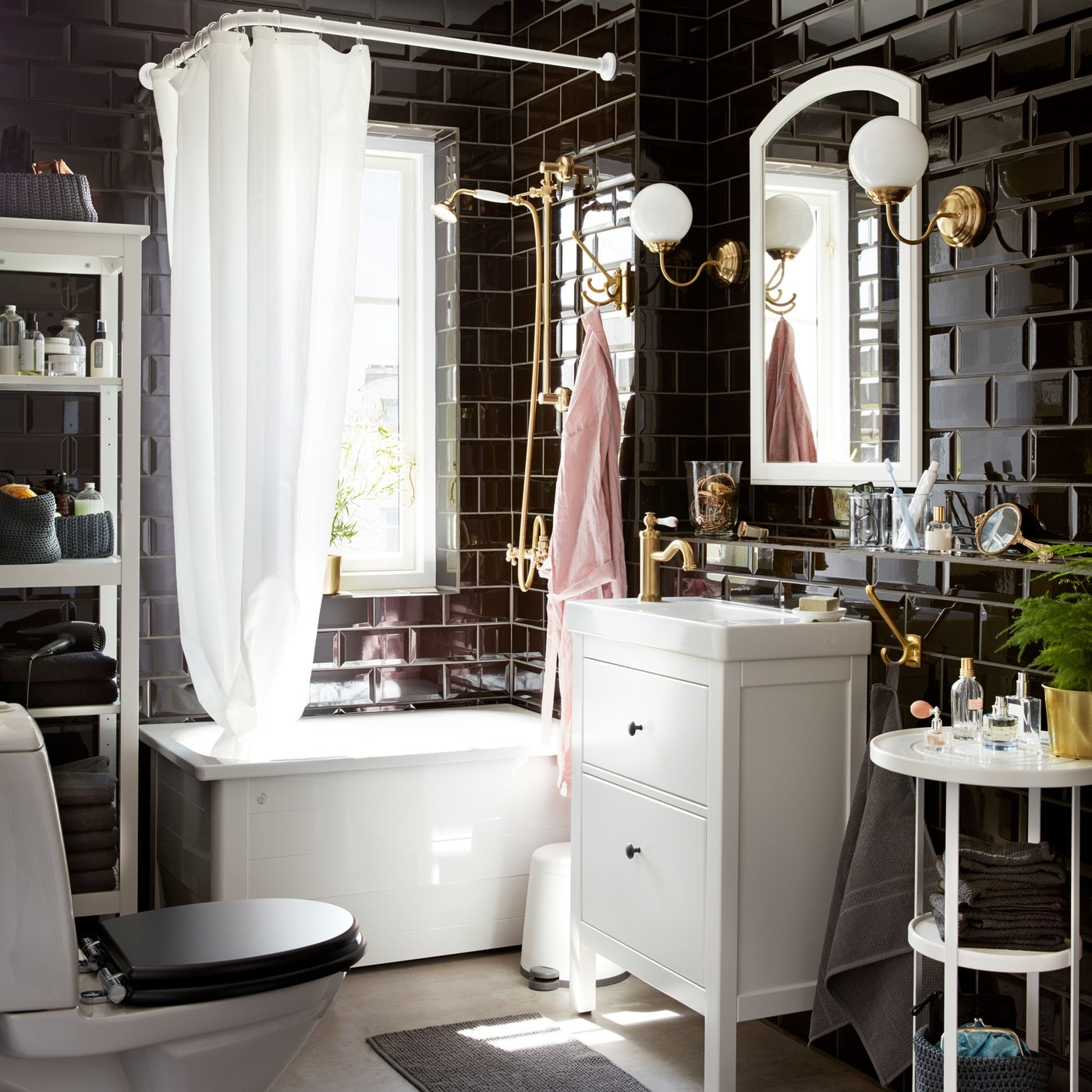 A dramatic and classic bathroom with glossy black tiles, white furniture, and brass-coloured wall lamps by the mirror.