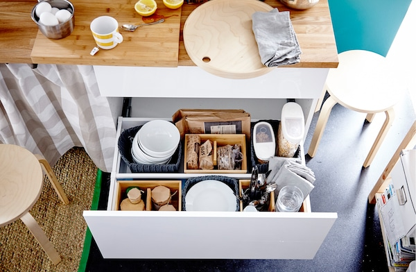 A drawer filled with containers of dry food stuff, bowls, plates, cutlery and glasses