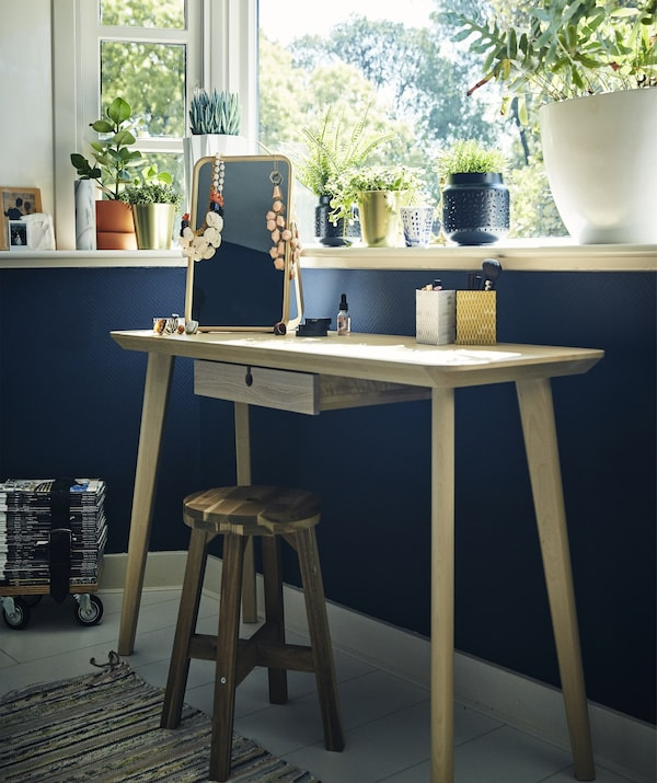 A dressing table and stool against a blue wall under a window.