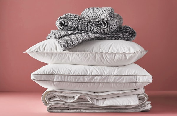 A duvet, pillows and blanket piled on top of one another.