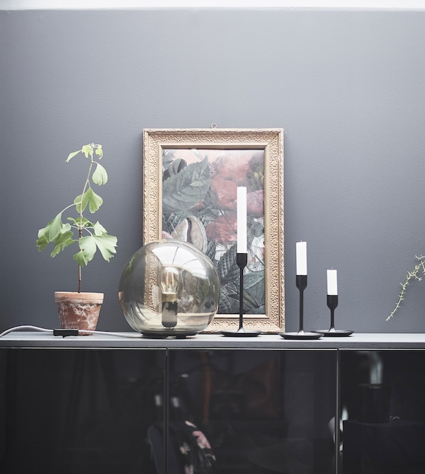 A FADO table lamp adds ambience to a bedroom display with candles, a painting, and plant on a cabinet.