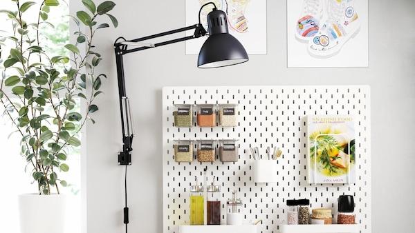 A falon lyukacsos tábla, előtte növény és egy asztali lámpa.