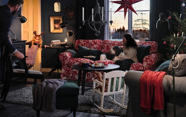A family and their dog sit in their living room, waiting for a small girl, peeking through the door, to put on a show.