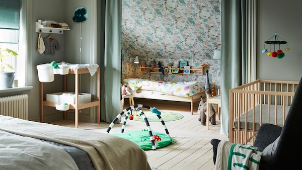 A family bedroom that contains a double bed, a SNIGLAR bed, cot and changing table, with curtains creating a private space.