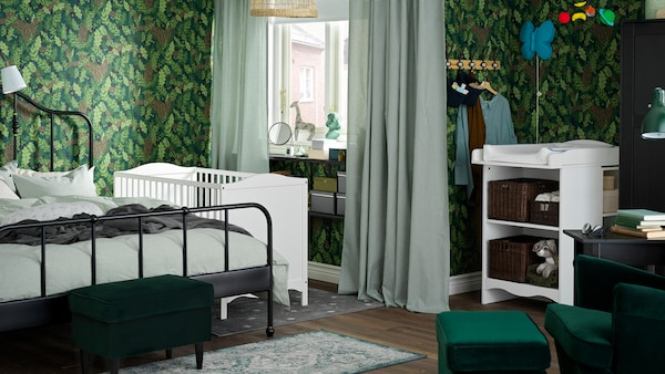 A family bedroom where a SAGSTUA double bed stands beside a white SMÅGÖRA cot and near a SMÅGÖRA changing table.