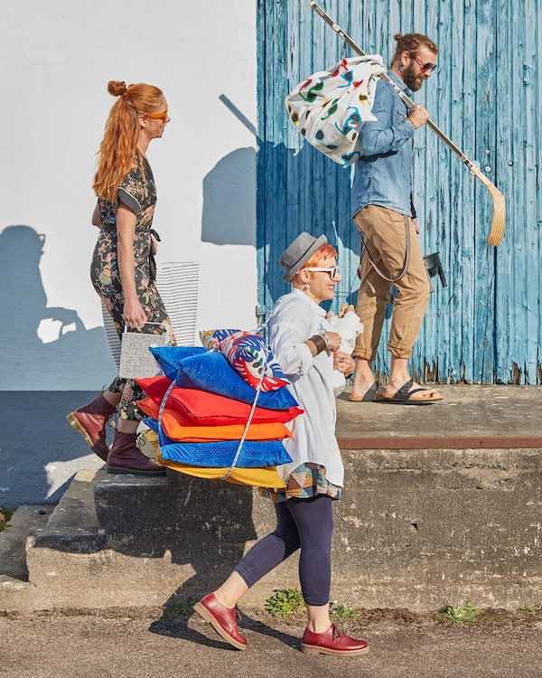 A family carrying summer party supplies in the sunshine, including cushions and fabric.