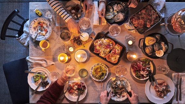 A family enjoying a candlelit meal with a variety of comfort food dishes on the dining table