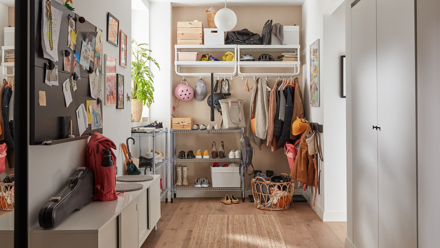 A family hallway with jackets hanging on white hooks and shelves, shoes on metal shelving units, a white storage bench.