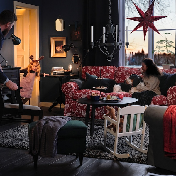 A family is gathering together in a festive living room.