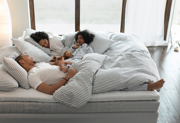 A family laying together in bed