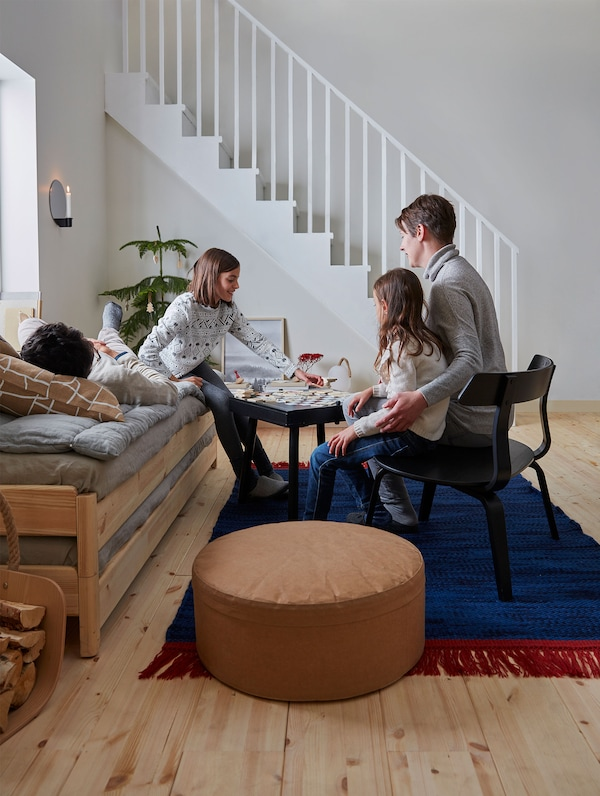 A family of four gathers in the living room playing at the VÄRMER board game table while sitting on a black chair and grey daybed.