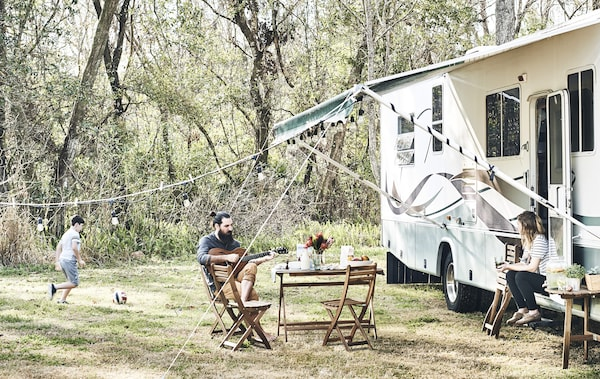A family relaxing outside a motorhome in a rural setting.