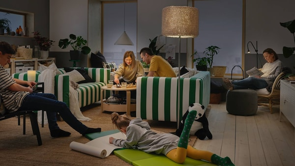 A family spend time together at home. NÄVLINGE pendant lamp, ISBRYTARE table lamp and NÄVLINGE floor lamp brighten the room.