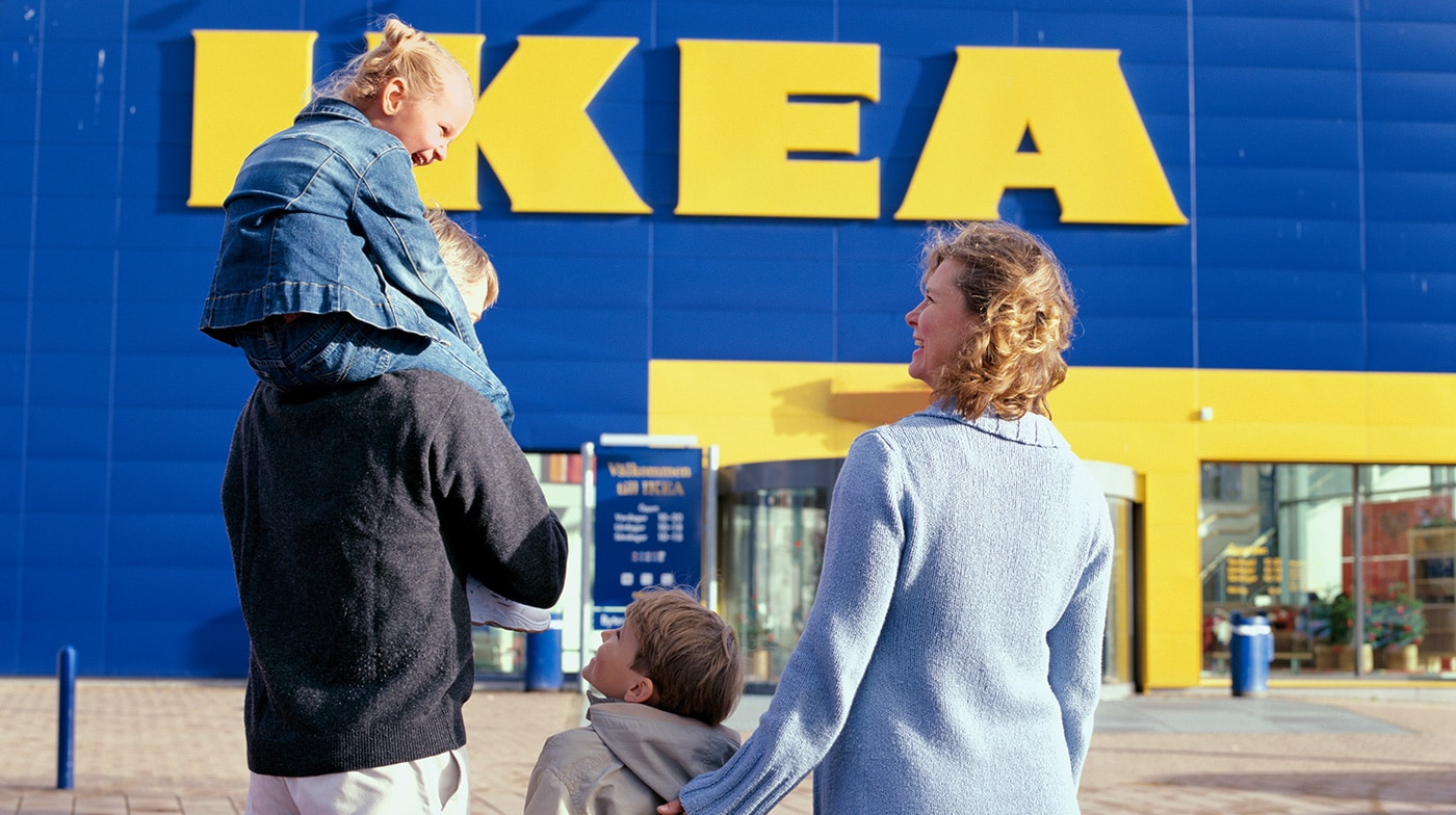 A family walking up to the entrance of an IKEA store