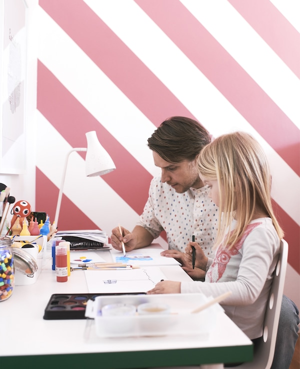 A father and daughter sat painting at a desk in front of brightly-coloured wallpaper.