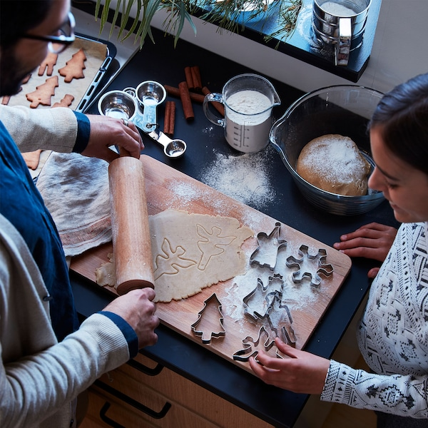 A father and his daughter are baking gingerbread cookies together using VÄRMER pastry cutters.
