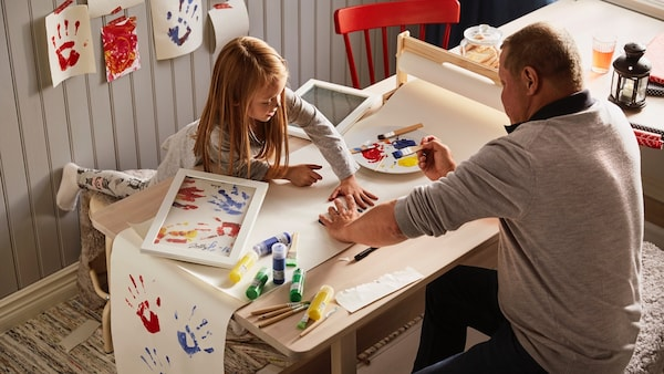 A father and his daughter are crafting together.