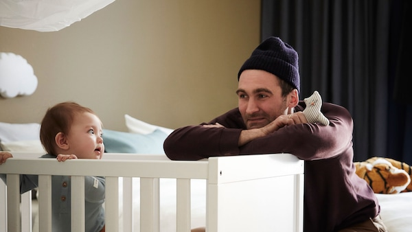 A father leaning on the edge of a white crib, looking at his baby, who is standing in the crib.