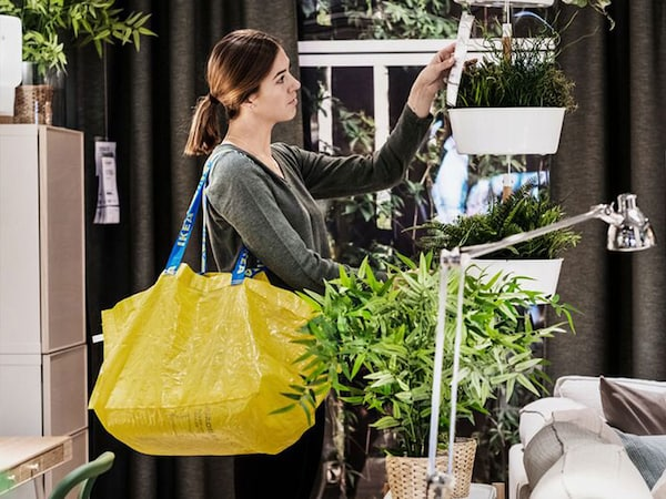 A female IKEA customer is shopping in-store with a yellow shopping bag. She is looking at a price tag for a white hanging plant holder.