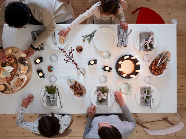 A festive scene is seen from above where a family gathers around a candle-lit dining table with cheese, figs and nuts.