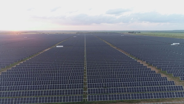 A field of endless solar panels outside with a cloudy sky above.