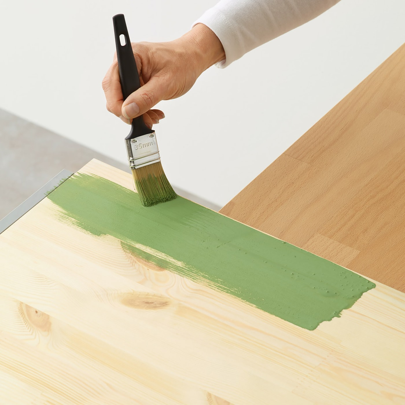 A FIXA paintbrush used to hand paint a wooden surface in green.