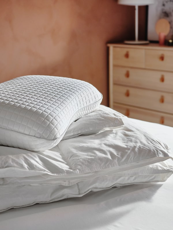 A FJÄLLARNIKA duvet and a KLUBBSPORRE ergonomic pillow are piled-up together on a bed in a sun-filled room.