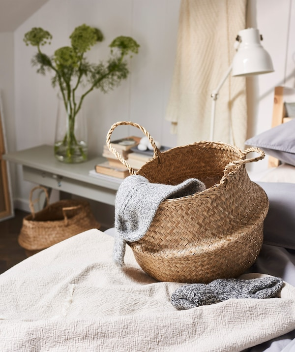 A FLÅDIS basket beside a bed with some warm throws stored inside.