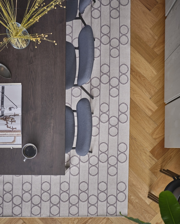 A flatwoven rug with a geometric pattern with circles lies beneath a black/dark brown dining table and grey chairs.