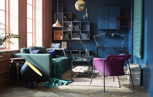 A flexible and comfortable living room that uses a modern shade of blue on the wall with a green sofa and textiles and wooden floor.