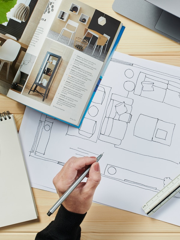 A floorplan and IKEA catalogue, with a hand holding a pencil above a work desk.