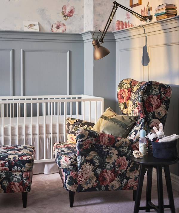 A floral armchair and footstool next to a baby's cot, with clamp light above.