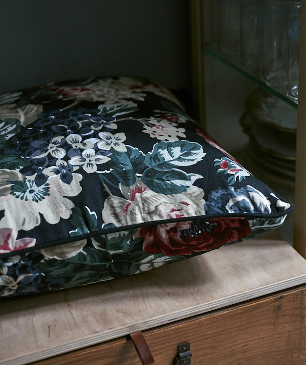 A floral-patterned cushion on a wooden box.