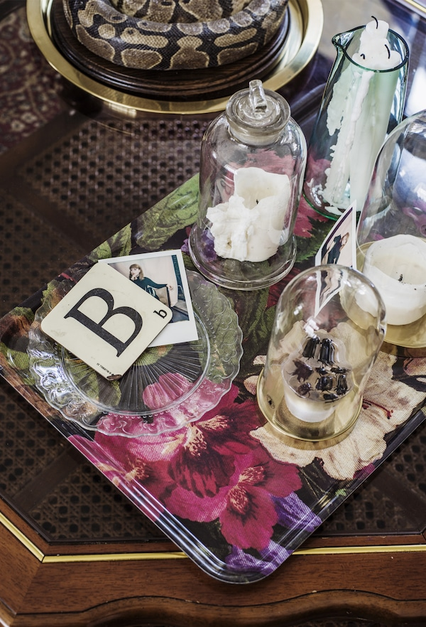 A floral tray with bell jars and candles.