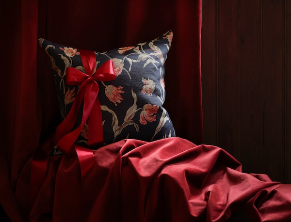 A flower patterned pillow with a red ribbon wrapped around it