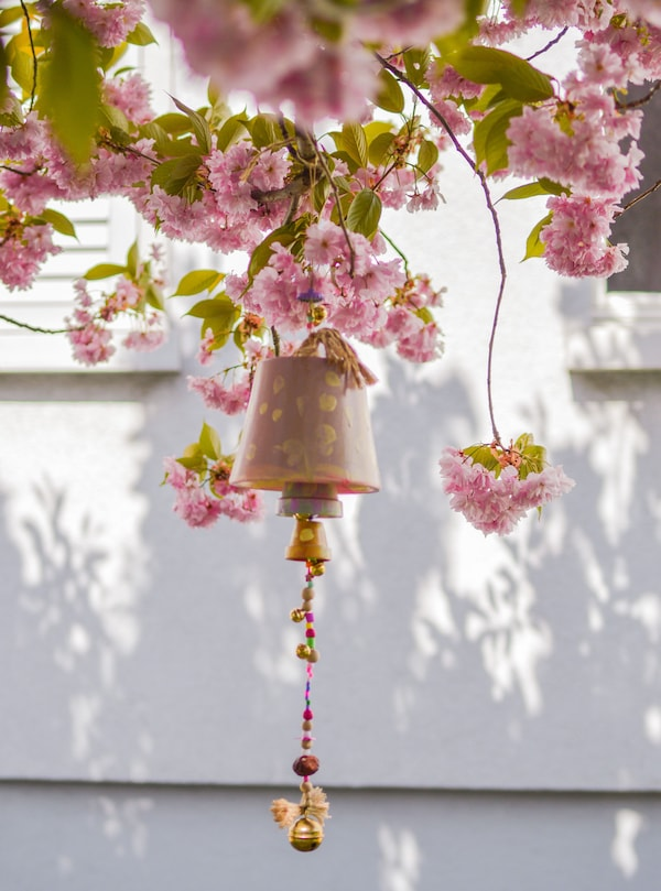 A flowerpot wind chime hanging from a tree