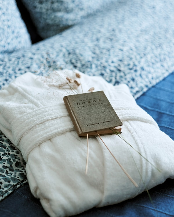 A fluffy white bathrobe folded on a bed with blue covers, there is also a vintage book on Norway displayed with grass stems.