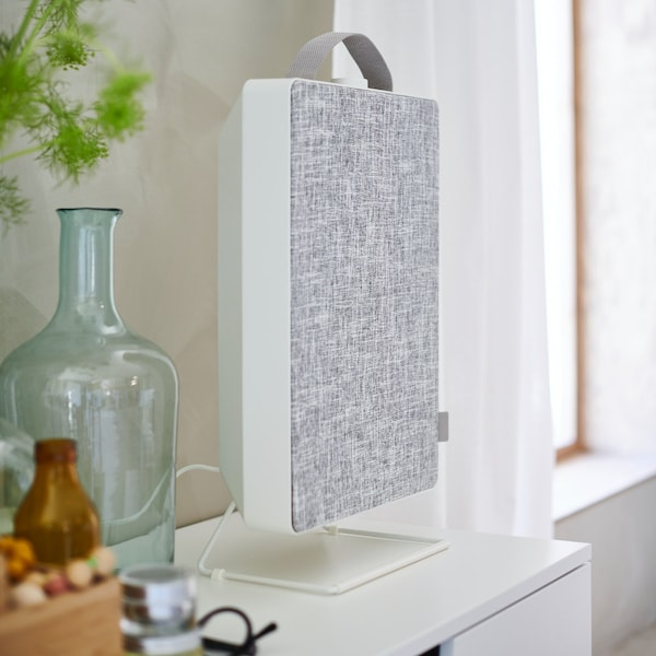 A FÖRNUFTIG air purifier on a white chest of drawers. There is a GLADOM tray table with a KORKEN bottle and glass next to it.